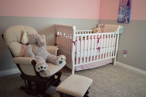 chambre petite fille avec lit à barreaux fauteuil avec une peluche éléphant posée dessus et repose pieds